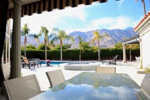 Large pool and outdoor dining area of luxury home. Reflection of mountain range and palm trees in table under cabana. No people. Day time.