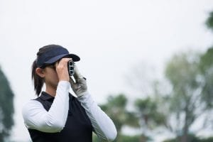 An Asian female golfer using a scope range to check the distance to the green